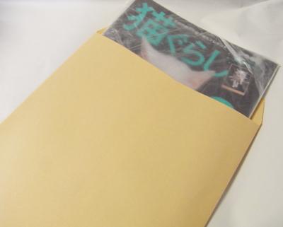 雑誌を封筒に入れて梱包する。